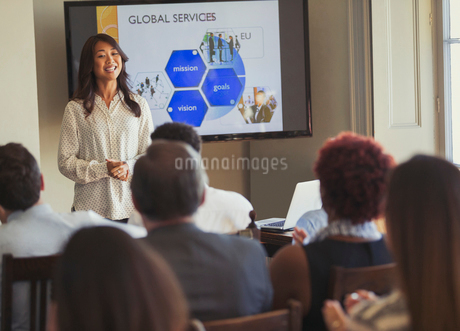 Smiling businesswoman leading business conference presentation at television screenの写真素材 [FYI02175820]
