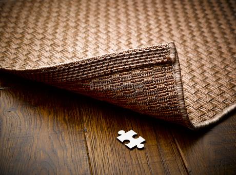 Puzzle piece hidden underneath rugの写真素材 [FYI02175825]