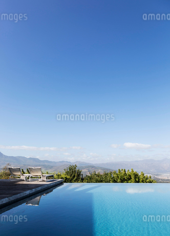 Tranquil luxury infinity pool with mountain view below sunny blue skyの写真素材 [FYI02175845]