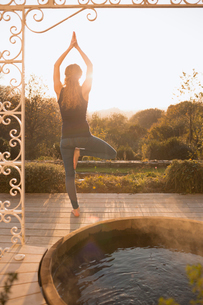 Woman practicing yoga tree pose on patio with hot tub and autumn tree viewの写真素材 [FYI02175859]