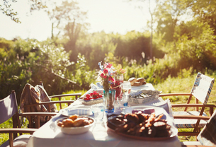 Food and flower bouquet on sunny garden party patio tableの写真素材 [FYI02175861]