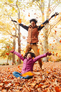 Playful mother and daughter throwing autumn leaves in parkの写真素材 [FYI02175872]