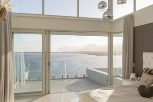 Sunny, tranquil modern luxury home showcase interior bedroom with ocean viewの写真素材 [FYI02175938]