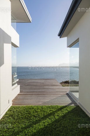 Modern home showcase exterior courtyard with sunny, tranquil ocean viewの写真素材 [FYI02175942]