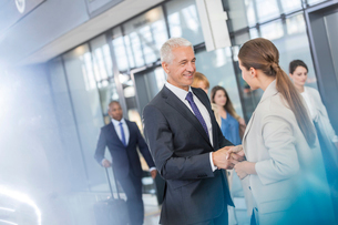 Business people greeting shaking hands in airportの写真素材 [FYI02175981]