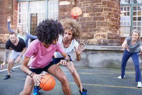 Friends playing basketball on urban basketball courtの写真素材 [FYI02175982]