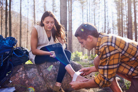 Young man hiking, bandaging girlfriend's ankle in woodsの写真素材 [FYI02176005]
