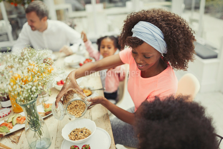 Mother pouring granola cereal for daughter at breakfast tableの写真素材 [FYI02176062]