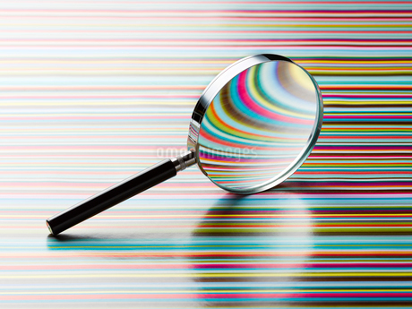Magnifying glass leaning on striped backgroundの写真素材 [FYI02176098]