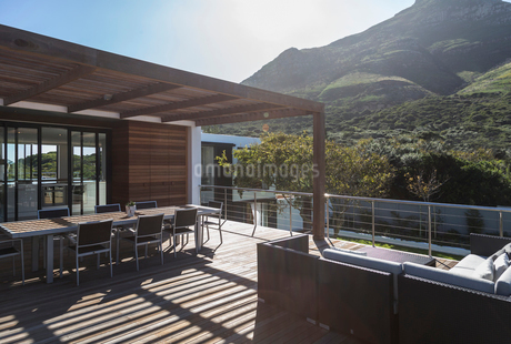 Sunny modern luxury home showcase exterior balcony patio with mountain viewの写真素材 [FYI02176129]