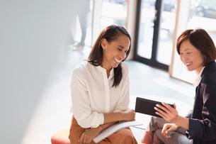 Smiling businesswomen using digital tablet in office lobbyの写真素材 [FYI02176134]