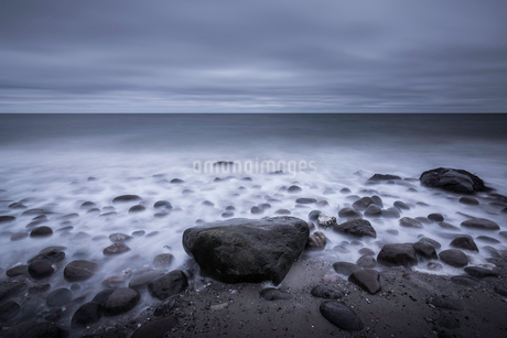 Tranquil overcast gray seascape and rocks on beach, Kalundborg, Denmarkの写真素材 [FYI02176143]
