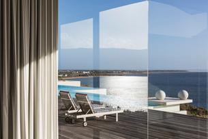 Window view of sunny modern luxury patio with infinity pool and ocean viewの写真素材 [FYI02176157]
