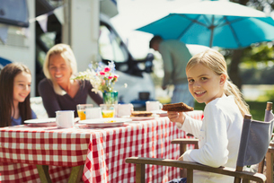 Portrait smiling girl eating breakfast with family outside sunny motor homeの写真素材 [FYI02176158]