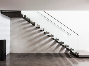 Modern, minimalist floating staircase in home showcase interior foyerの写真素材 [FYI02176162]