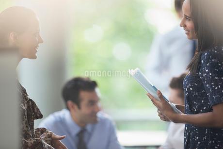 Businesswomen with paperwork talking in meetingの写真素材 [FYI02176208]