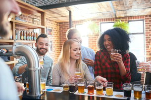 Friends sampling, drinking beer in pubの写真素材 [FYI02176215]