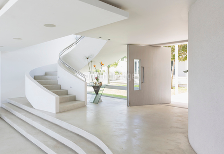White foyer and spiral staircase in modern luxury home showcase interiorの写真素材 [FYI02176239]