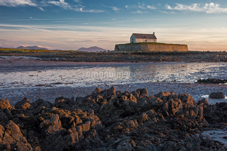Tranquil medieval island church at low tide, St Cwyfans Church, Anglesey, Walesの写真素材 [FYI02176247]