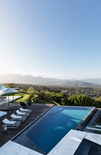 Home showcase exterior infinity pool and patio with mountain view under sunny blue skyの写真素材 [FYI02176257]
