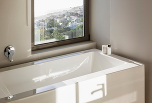 Sunny reflection over modern white bathtub below windowの写真素材 [FYI02176290]
