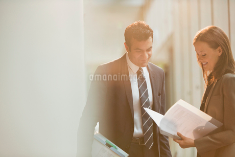 Businessman and businesswoman reviewing paperwork in office lobbyの写真素材 [FYI02176308]