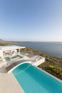 Sunny, tranquil modern luxury home showcase infinity pool with footbridge and ocean view under blueの写真素材 [FYI02176312]