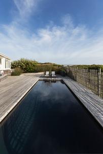 Dark luxury swimming pool under sunny blue skyの写真素材 [FYI02176339]