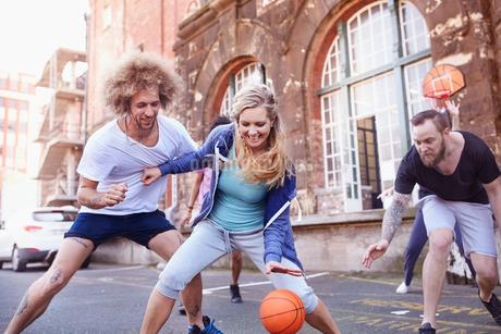 Friends playing basketball on urban basketball courtの写真素材 [FYI02176356]