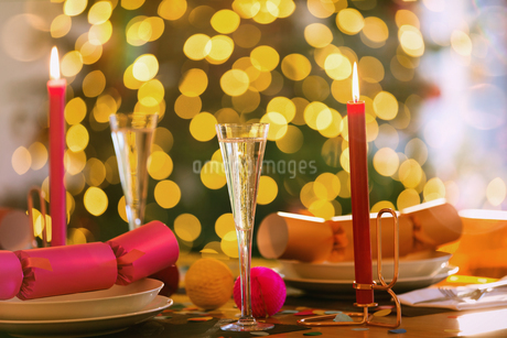 Champagne flutes, candles and Christmas crackers on dining tableの写真素材 [FYI02176395]