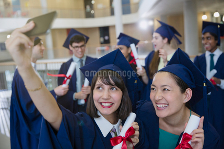 College women graduates in cap and gown taking selfie with diplomasの写真素材 [FYI02176399]
