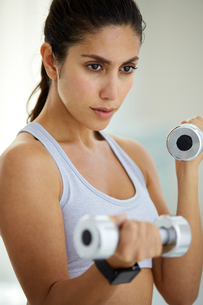 Determined brunette woman doing biceps curls with dumbbellsの写真素材 [FYI02176410]
