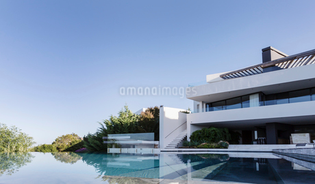 Tranquil home showcase interior with infinity pool under sunny blue skyの写真素材 [FYI02176425]
