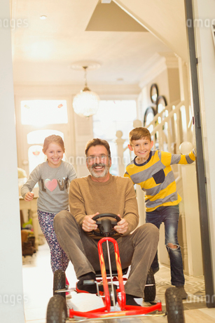 Portrait smiling children pushing father on toy car in foyer corridorの写真素材 [FYI02176429]
