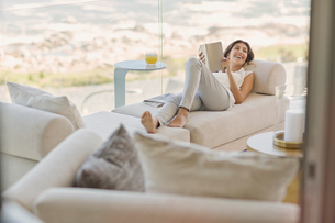 Smiling woman reading book relaxing on chaise loungeの写真素材 [FYI02176434]