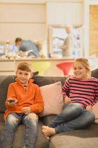Brother and sister watching TV on living room sofaの写真素材 [FYI02176444]