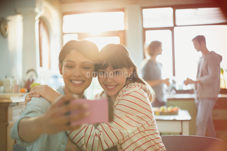 Young women friends roommates hugging taking selfie with camera phoneの写真素材 [FYI02176476]