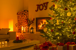 Ambient fireplace and candles in living room with Christmas treeの写真素材 [FYI02176479]