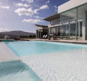 Sunny, tranquil modern luxury home showcase exterior with swimming poolの写真素材 [FYI02176497]