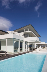 Sunny, tranquil modern luxury home showcase exterior with swimming pool under blue skyの写真素材 [FYI02176498]
