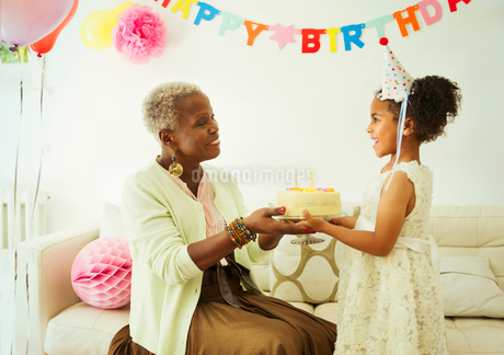 Grandmother and granddaughter holding cake at birthday partyの写真素材 [FYI02176509]