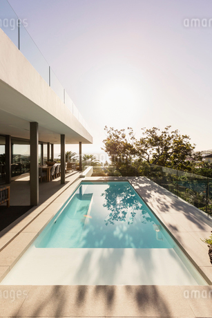 Tranquil lap swimming pool outside modern luxury home showcase exteriorの写真素材 [FYI02176527]