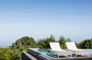 Lounge chairs and infinity pool under tranquil, sunny blue skyの写真素材 [FYI02176538]