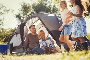Parents watching happy daughters running around sunny campsite tentの写真素材 [FYI02176562]
