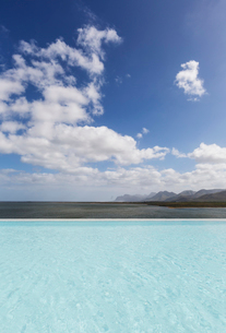 Sunny, tranquil infinity pool with ocean view under blue sky with cloudsの写真素材 [FYI02176572]