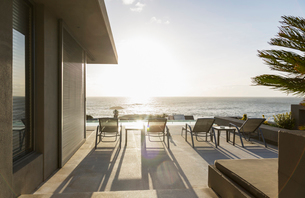 Lounge chairs on sunny luxury patio with ocean viewの写真素材 [FYI02176613]