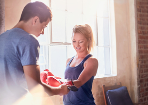 Trainer helping young female boxer putting on boxing gloves in studioの写真素材 [FYI02176621]