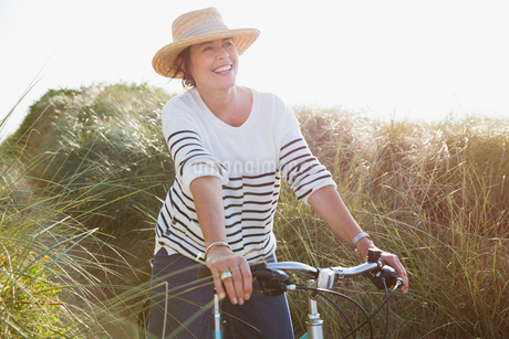 Smiling mature woman riding bicycle on sunny beach grass pathの写真素材 [FYI02176637]