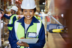 Portrait smiling female worker with clipboard in distribution warehouseの写真素材 [FYI02176672]