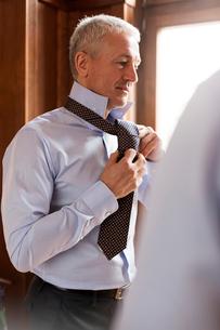 Businessman trying on tie in menswear shopの写真素材 [FYI02176695]